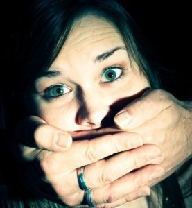 woman with man's hands over mouth