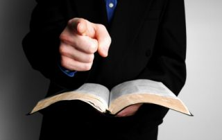 man with Bible pointing his finger accusingly
