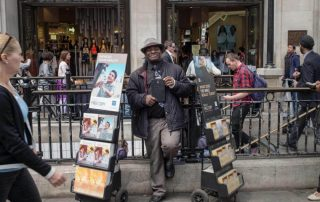 On of Jehovah's Witnesses on street with magazine stand