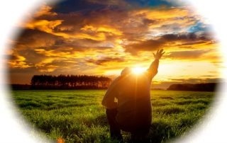 Man kneeling with hand outstretched to the sky as the sun sets