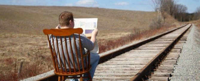 man reading newspaper in rocking chair on railroad track