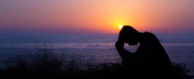 man praying by the sea