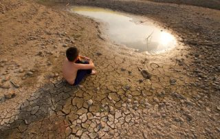 child sits on cracked earth - global warming concept