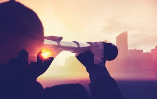 Business man in suit with cityscape montage. The man is unrecognizable and you cannot see his face. He is superimposed onto a city skyline at sunset. He is holding a telescope looking into the city. Success, vison concept with copy space.