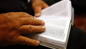 person reading New World Translation of the Bible
