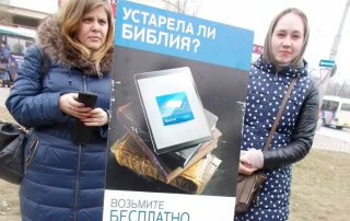 Two Jehovah's Witness women stand with information cart
