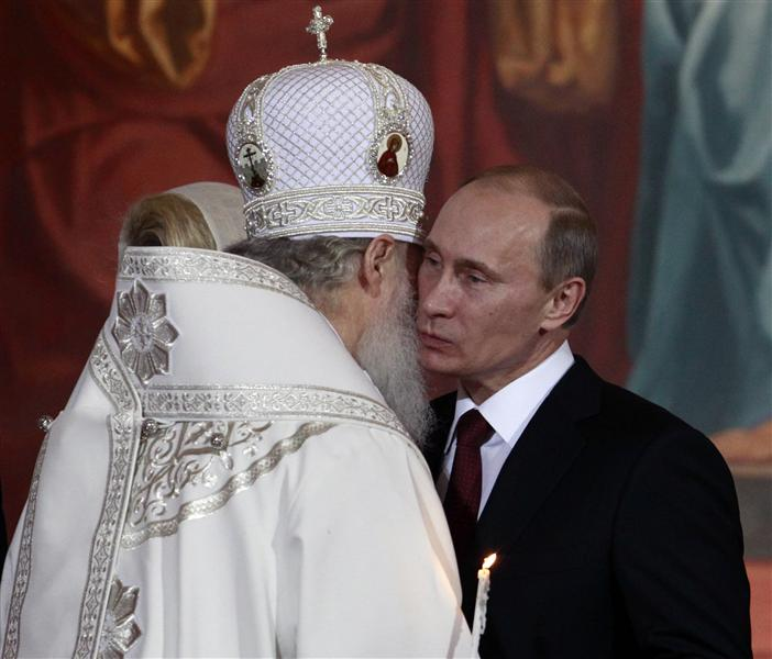 Russia's Prime Minister Vladimir Putin (R) kisses Patriarch of Moscow