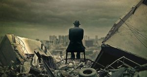 man sitting amidst rubble at the end of the world