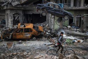 Iraqi boy rides bike in ruins of Mosul