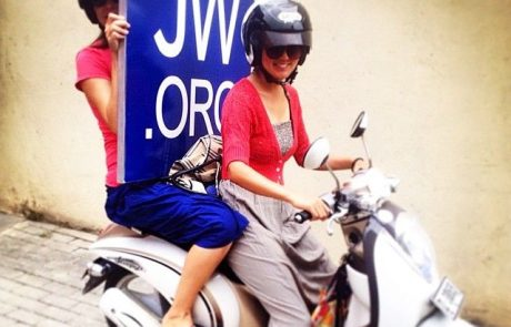 Two female Jehovah's Witnesses on scooter with JW.org sign